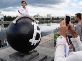 A girl poses for a photograph on a stone sphere monument that unidentified persons have painted with the white Bitcoin cryptocurrency symbol in Oktyabrskaya Square, Yekaterinburg, Russia.