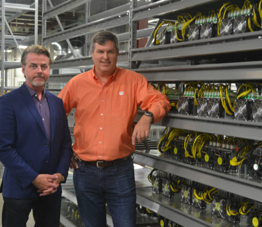 Michael Bolick, left, and David Pence, two of the managing directors of Treis Blockchain LLC, stand by one of what eventually will be a warehouse full of racks of cryptocurrency mining servers. (Photo/Ross Norton)