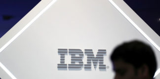 © Reuters. FILE PHOTO: A man stands near an IBM logo at the Mobile World Congress in Barcelona