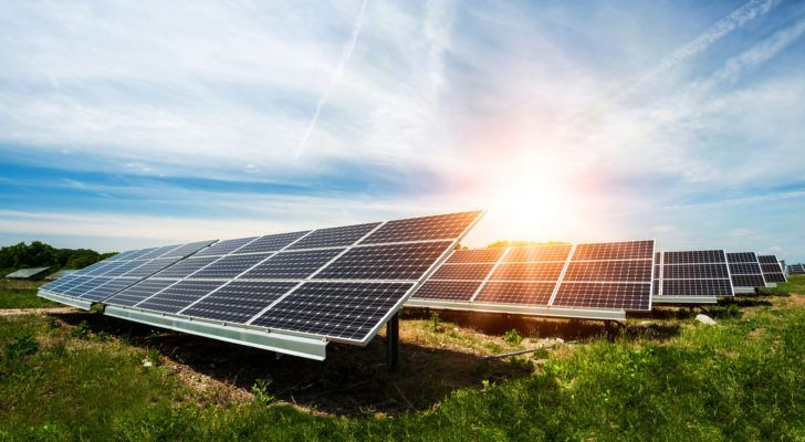 Solar energy panels are arranged in a green field under a sunny sky.